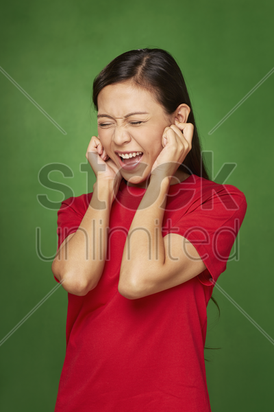 woman covering ears using her hands stock photo