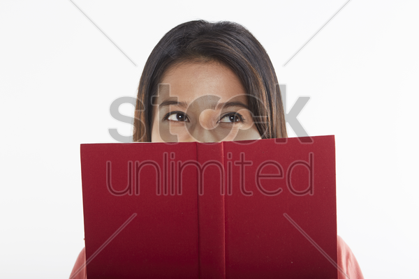 woman covering half her face with a book stock photo
