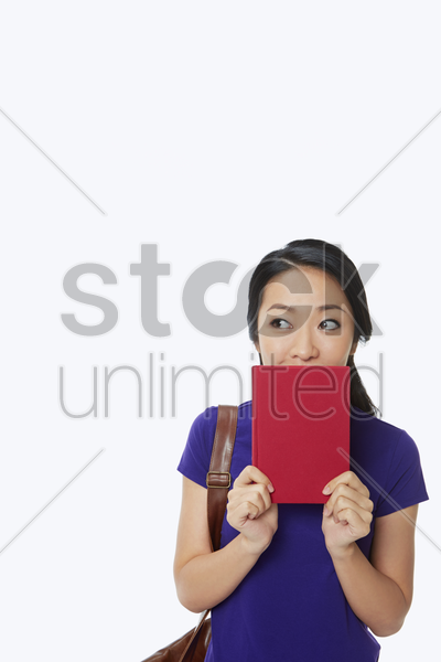 woman covering her mouth with a book stock photo