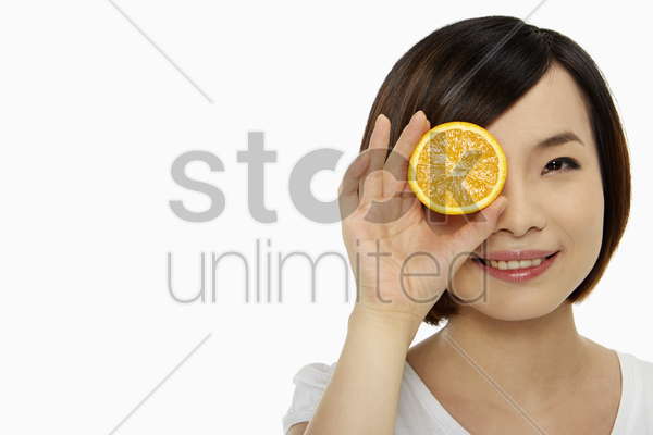 woman covering one eye with an orange stock photo