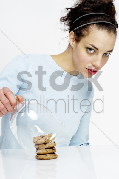 woman covering up a stack of cookies stock photo