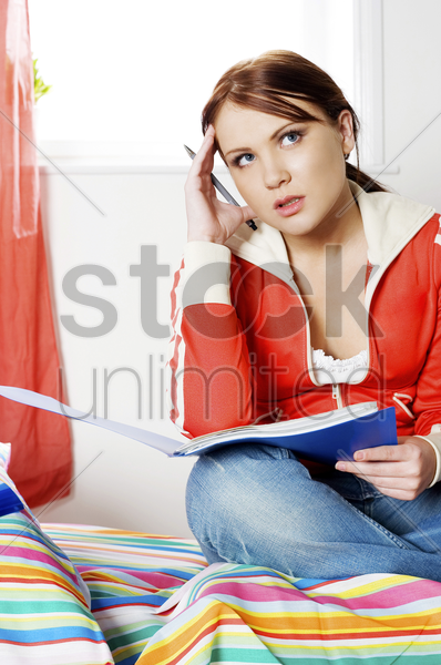 woman cracking for ideas in her bedroom stock photo