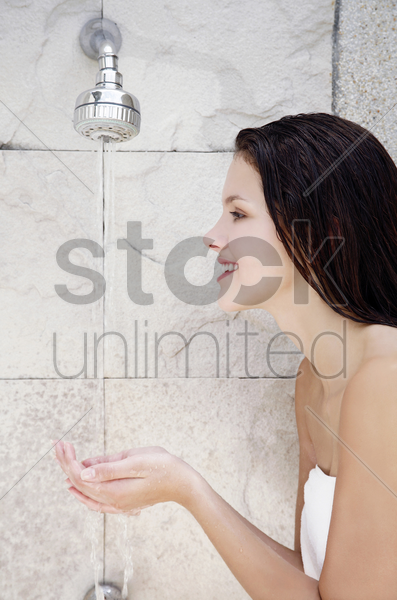 woman cupping water from the shower stock photo
