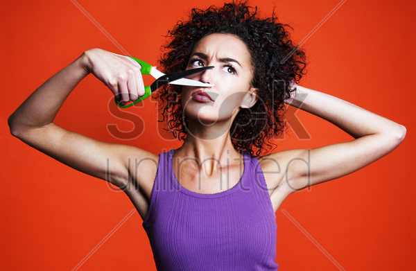 woman cutting her nose with a scissors stock photo