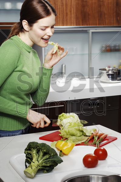 woman cutting vegetables in the kitchen stock photo