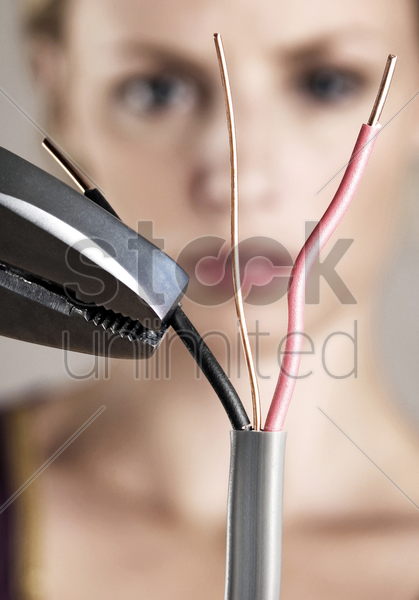 woman cutting wire with pliers stock photo