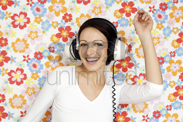 woman dancing while listening to music on the headphones stock photo