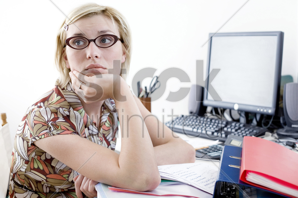 woman daydreaming at desk in a home office stock photo