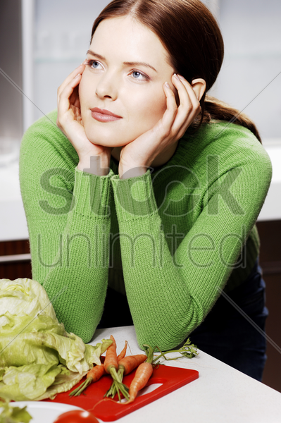 woman daydreaming in the kitchen stock photo