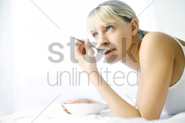 woman daydreaming while eating on the bed stock photo