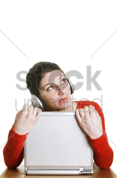 woman daydreaming while listening to music on the headphones stock photo