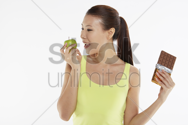 woman deciding between an apple and a chocolate bar stock photo