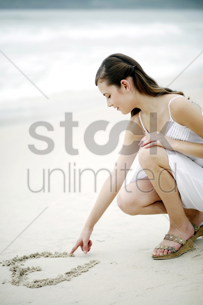 woman drawing a heart shape on the sand stock photo