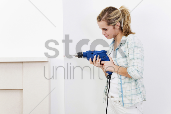 woman drilling the wall stock photo