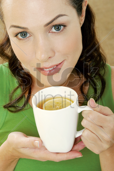woman drinking a cup of lemon tea stock photo