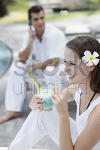 woman drinking cocktail, man talking on the phone in the background stock photo