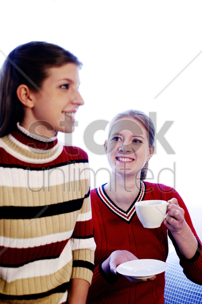 woman drinking coffee while looking at her daughter stock photo