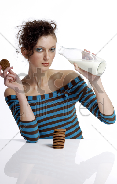 woman drinking milk while holding biscuit stock photo