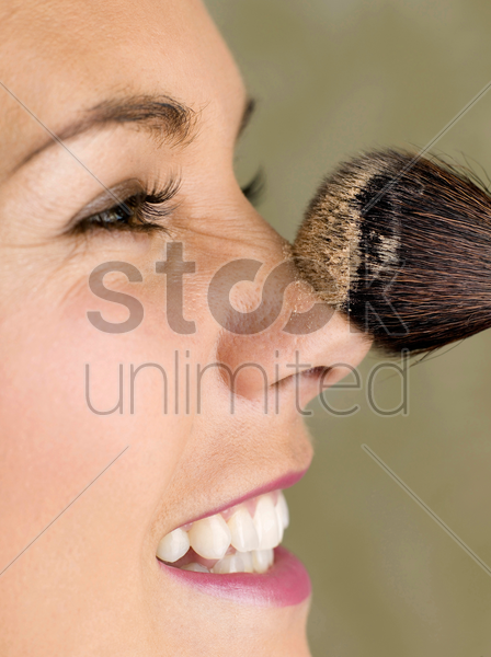 woman dusting powder on her face stock photo