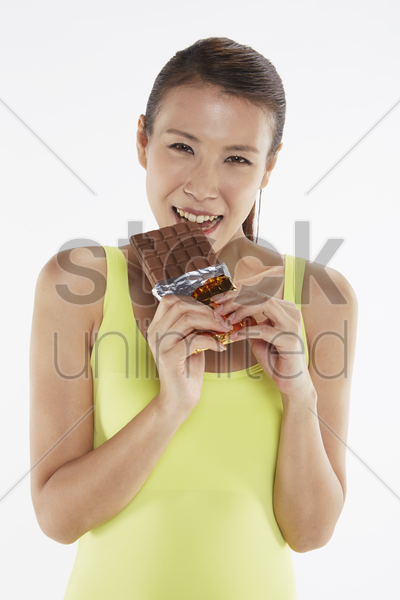 woman eating a bar of chocolate stock photo