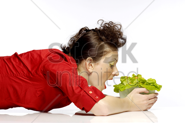 woman eating a bowl of salad stock photo
