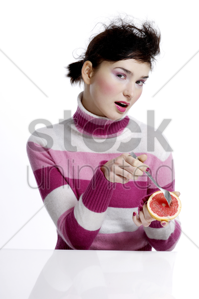 woman eating blood orange stock photo
