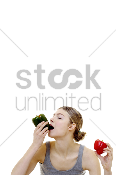 woman eating capsicum stock photo
