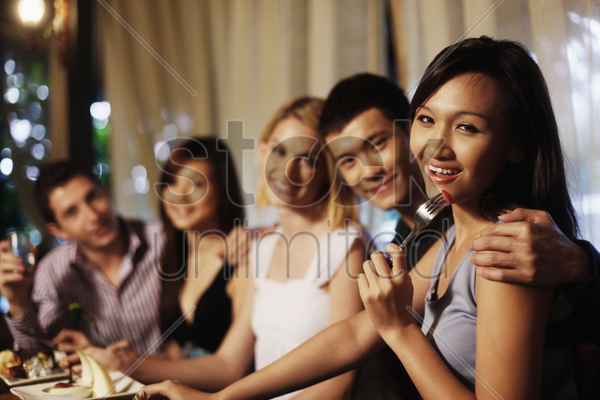 woman eating cherry tomato, friends in the background stock photo