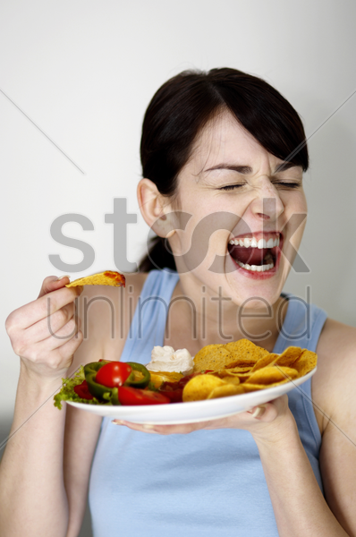 woman eating chips stock photo