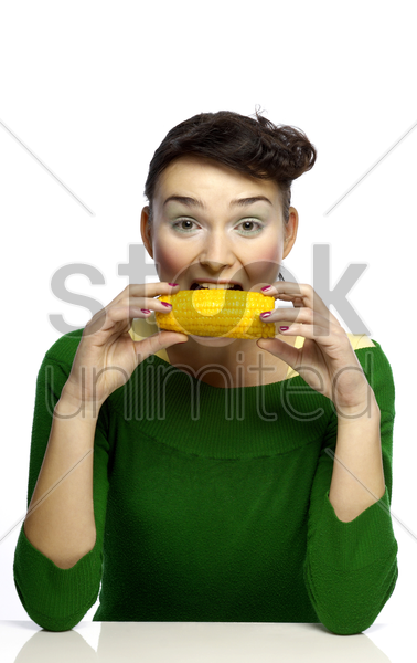 woman eating corn stock photo