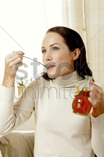 woman eating honey stock photo