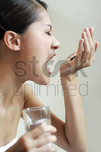 woman eating pills while holding a glass of water stock photo