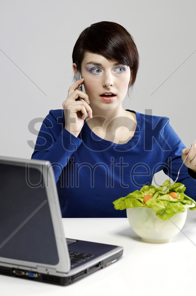 woman eating salad while talking on the hand phone stock photo