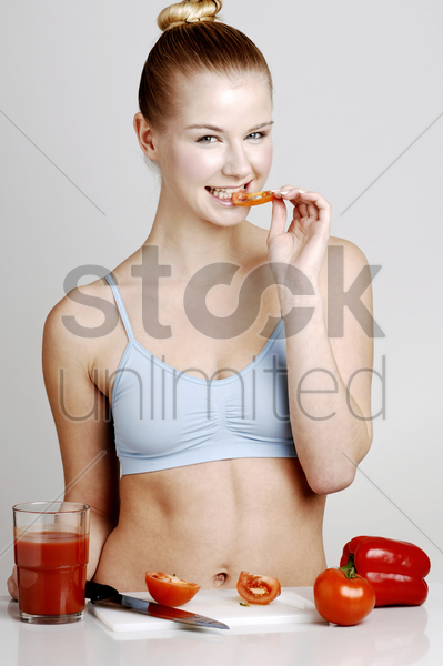 woman eating sliced tomato stock photo