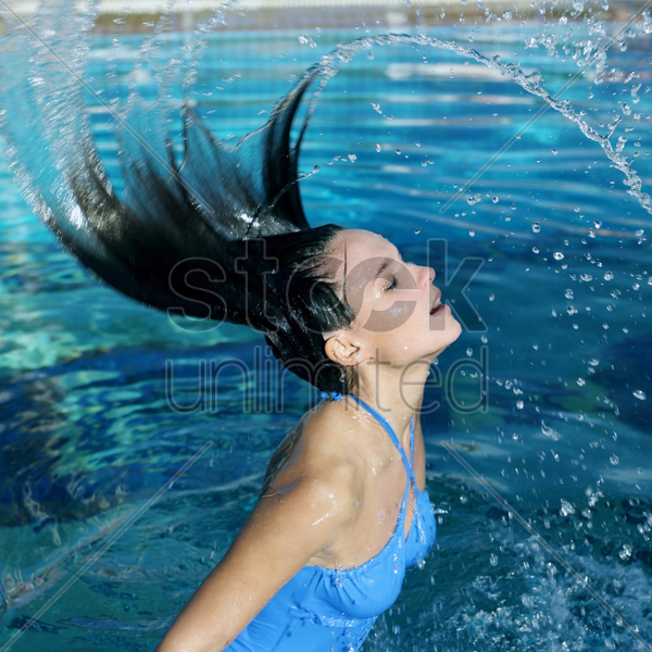 woman emerging from under the water splashing her hair stock photo