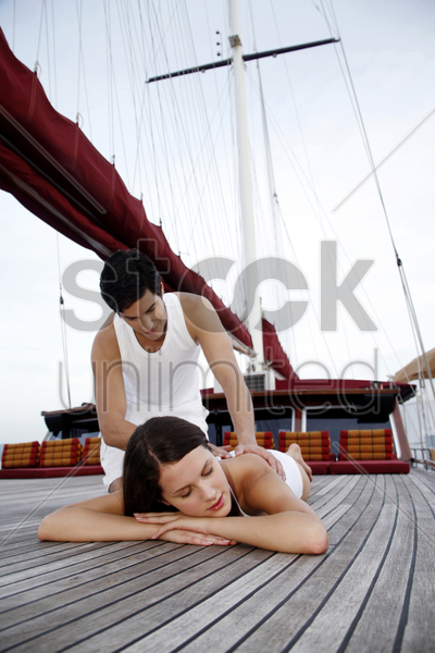 woman enjoying a body massage from her boyfriend stock photo
