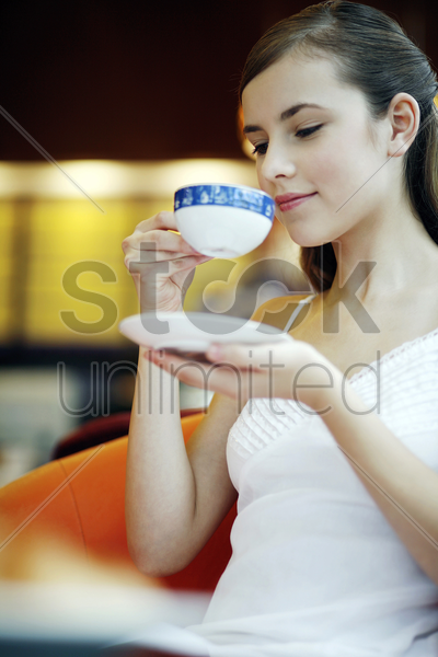 woman enjoying a cup of aromatic coffee in a cafe stock photo