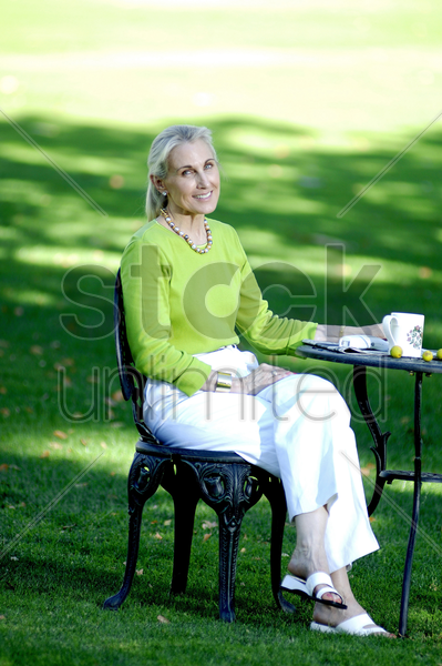 woman enjoying a cup of coffee in the garden stock photo