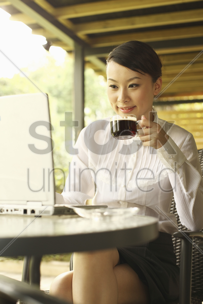 woman enjoying a cup of coffee while using laptop in cafe stock photo