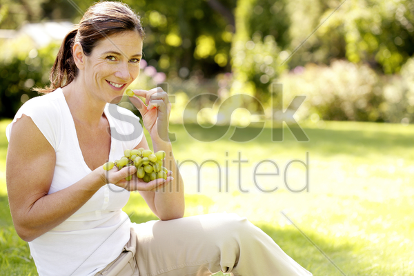 woman enjoying green grapes in the park stock photo