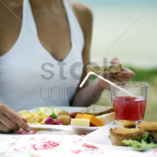 woman enjoying her meal by the beach side stock photo