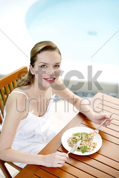 woman enjoying her meal by the pool side stock photo