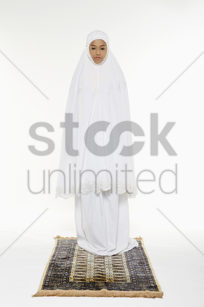 woman facing the qiblah with the intention of performing a prayer stock photo