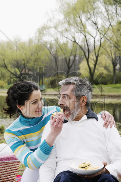 woman feeding her husband while picnicking in the park stock photo