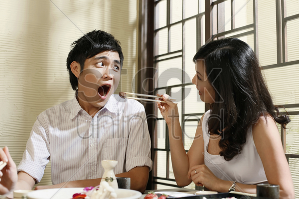woman feeding man with grilled beef stock photo
