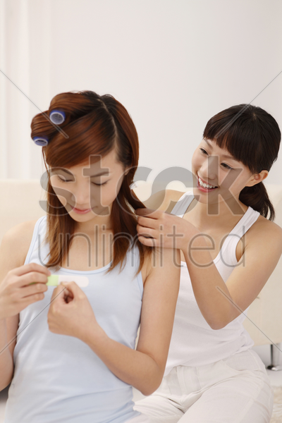 woman filing her fingernails while her friend styling her hair stock photo