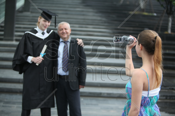 woman filming father and graduate son with a video camera stock photo
