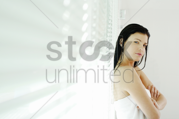 woman folding her arms while leaning against window blinds stock photo