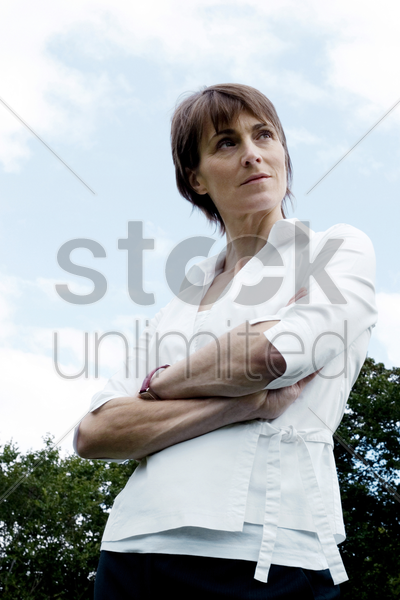 woman folding her arms while thinking stock photo