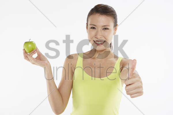 woman gesturing and holding a green apple stock photo